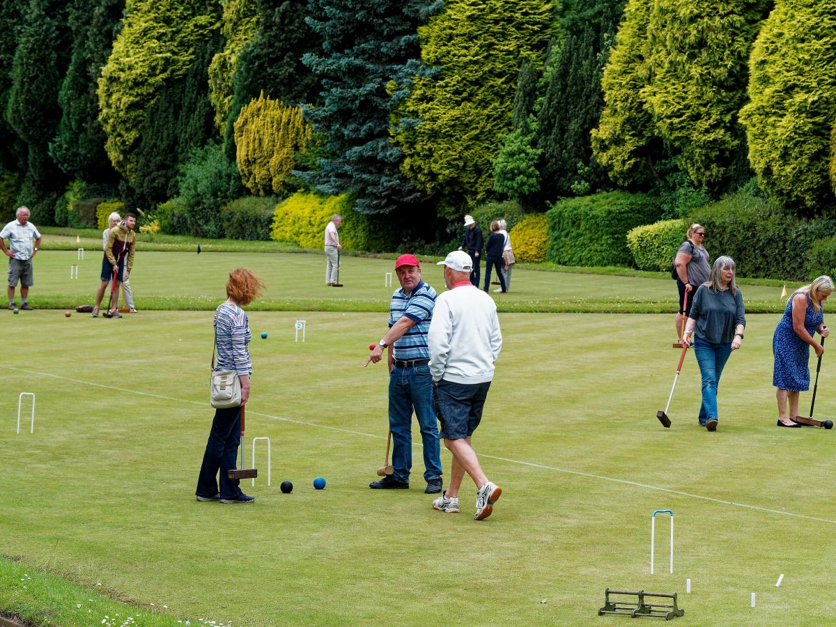 Visitors in action - playing on lawns 6-7 with fine, varied evergreens behind