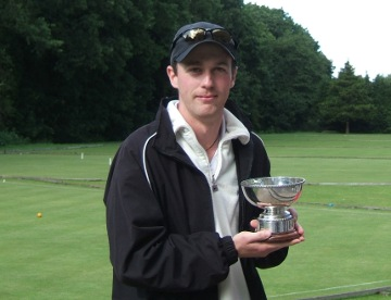 Young guy with peaked cap holding a silver trophy